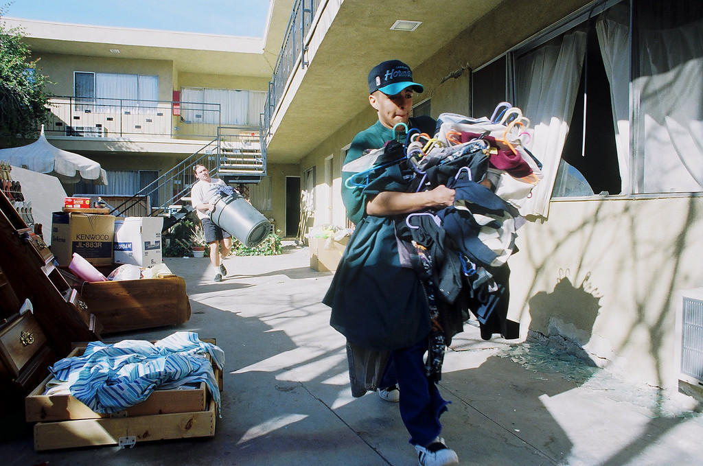 . Rene Valenzuela carries an armload of clothes out of the condemned Mountain Terrace apartments on Walnut Street in Newhall.   Los Angeles Daily News file photo