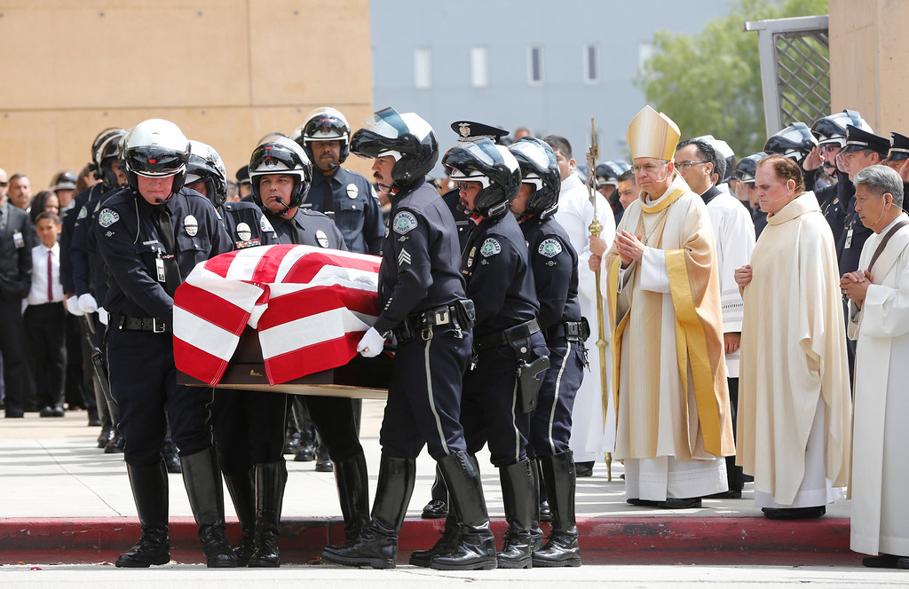 . Pallbearers carry the coffin of Los Angeles Police Dept. motorcycle officer Chris Cortijo into a hearse after a funeral service at the Cathedral of Our Lady of the Angels Tuesday morning, April 22, 2014, in Los Angeles. Hundreds of fellow law enforcement officers turned out to mourn 51-year-old officer, who died after he was struck by a motorist allegedly under the influence of cocaine on April 5.(AP Photo/Damian Dovarganes)