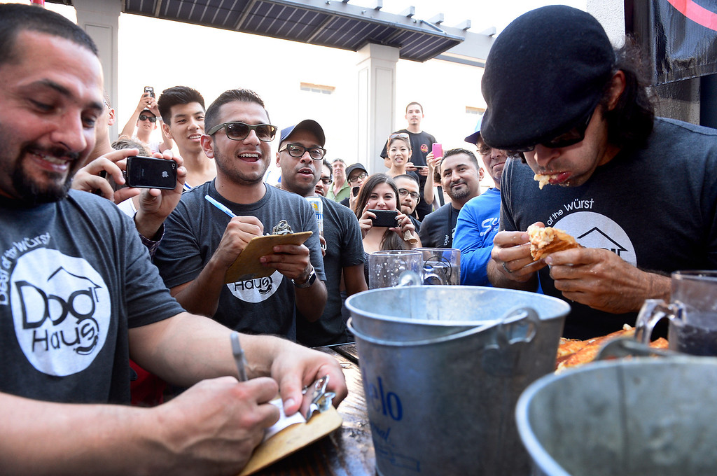 . Naader Reda, of Victorville, competes in the First Annual Hot Dog Eating Competition at Dog Haus Biergarten in Old Pasadena Saturday, July 6, 2013. Reda came in third and was beat by Jimmy Lin who ate 11 dogs, 3 during a tiebreaker. (SGVN/Staff Photo by Sarah Reingewirtz)