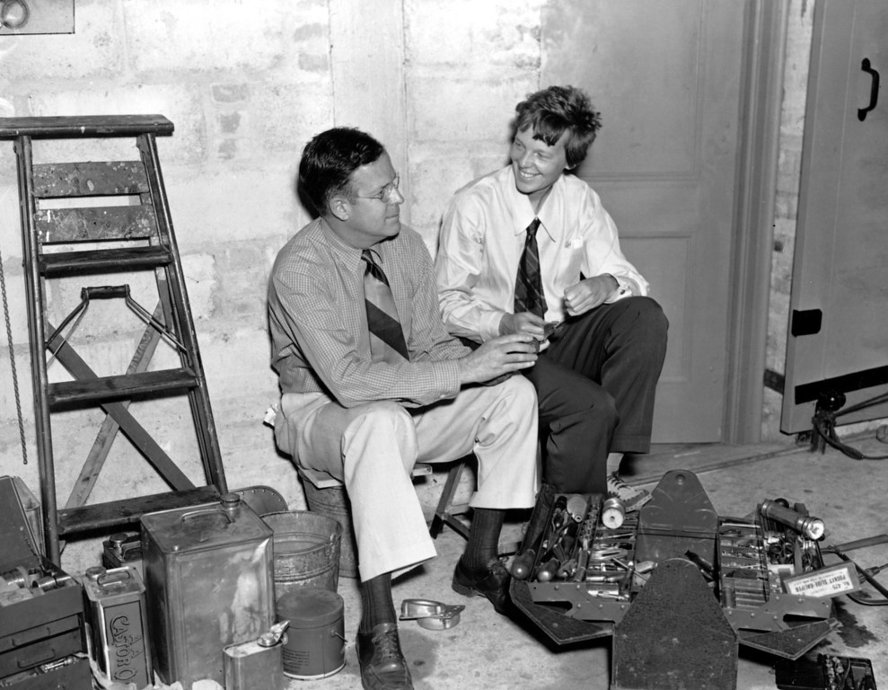 . American aviatrix Amelia Earhart, right, and her husband, publisher George Putnam, talk over plans for Earhart\'s second attempt to fly around the world.  They are in a hangar where Earhart\'s plane Electra is being prepared for flight in Miami, Fla., May 29, 1937.  (AP Photo)