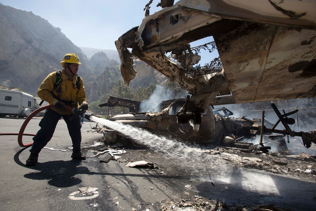 . A firefighter puts out a fire while the mobile homes are burning after after a blaze broke out during morning rush hour along U.S. 101 in the Camarillo area about 50 miles west of Los Angeles, May. 2, 2013, in Camarillo, Calif.  A wildfire fanned by gusty Santa Ana winds raged along the fringes of Southern California communities on Thursday, forcing evacuation of homes and a university while setting recreational vehicles ablaze. (AP Photo/Ringo H.W. Chiu)