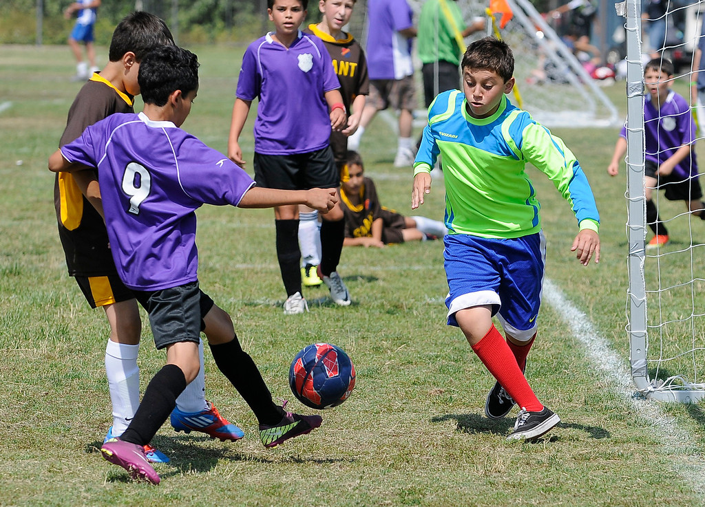 . Tom Zaduryan, #9 from team LA, shoots the ball while Alex Kevorkian, the goalie from Shant, moves in to block the shot. The kids were playing in the months-long Homenetmen Navasartian Games, an Armenian athletic competition that involves thousands of competitors, concluded Saturday at Birmingham High School in Van Nuys, CA. 7/6/2013(John McCoy/LA Daily News)