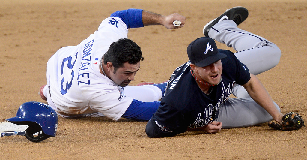 . The Atlanta Braves\' Elliot Johnson outs Los Angeles Dodgers\' Adrian Gonzalez at second before Yasiel Puig stole the base on an overthrow during game 3 of the NLDS at Dodger Stadium Sunday, October 6, 2013. (Photo by Sarah Reingewirtz/Los Angeles Daily News)