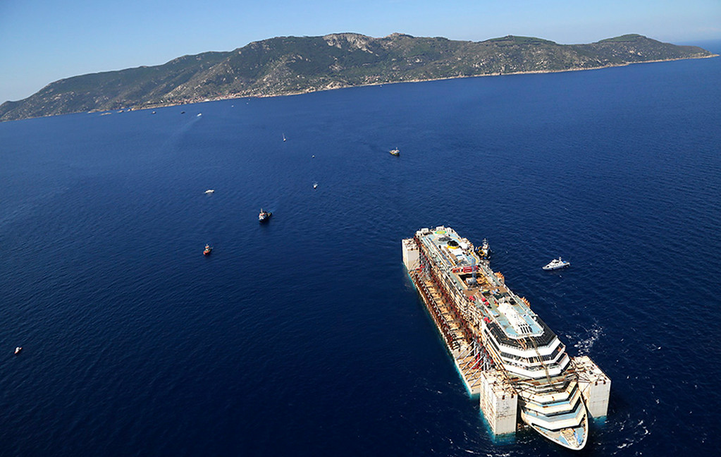 . In this aerial picture provided by the Italian Civil Protection Department, the wreck of the Costa Concordia is towed by two tugboats as it leaves behind the tiny Tuscan island of Isola del Giglio,  Italy, Wednesday, July 23, 2014. The Costa Concordia cruise liner has begun its final voyage away from the tiny Italian island where it capsized on Jan. 13, 2012, killing 32 people. (AP Photo/Courtesy of the Italian Civil Protection Department, ho)