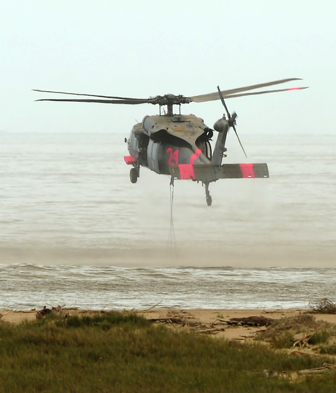 . A military helicopter drops a water bucket in the ocean during the fire fighting operation at Naval Base Ventura County, Friday, May 3, 2013. (Michael Owen Baker/Los Angeles Daily News)