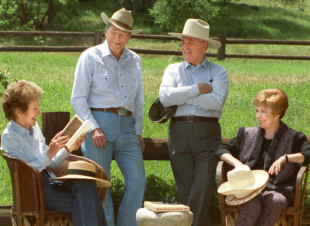 . 5/3/92--Santa Barbara--Former United States President Ronald Reagan, left and former Soviet President Mikhail Gorbachev don cowboy hats while enjoying a quiet moment with wives Nancy, left and Raisa Sunday on Reagan\'s Rancho del Ceilo, a 688-acre spread in the mountains 30 miles north of Santa Barbara, California. (Los Angeles Daily News file photo)