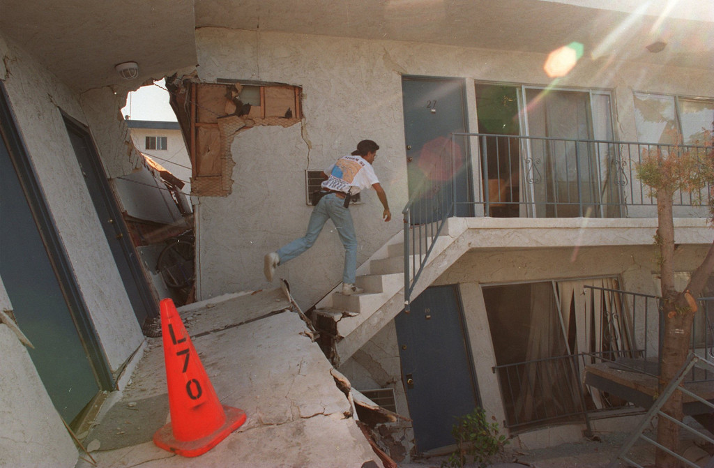 """. Robin Purcell makes his way to his daughter\'s apartment on Plummer St in Northridge to recover some of her possessions.  The Northridge quake hit at 4:31 the morning of Jan. 17, 1994, a powerful jolt that flattened buildings, destroyed homes, damaged freeways, ignited fires and disrupted water and power.  The 6.7-magnitude Northridge Earthquake also killed nearly three dozen people, injured 8,700 more, caused some $20 billion in damage and shattered the nerves of millions of Southern California residents.  \""""It was like the devil was waking up ... it was a horrifying feeling,\"""" said one of the quake victims quoted in a Daily News story on Jan. 18.  Daily News File Photo"""
