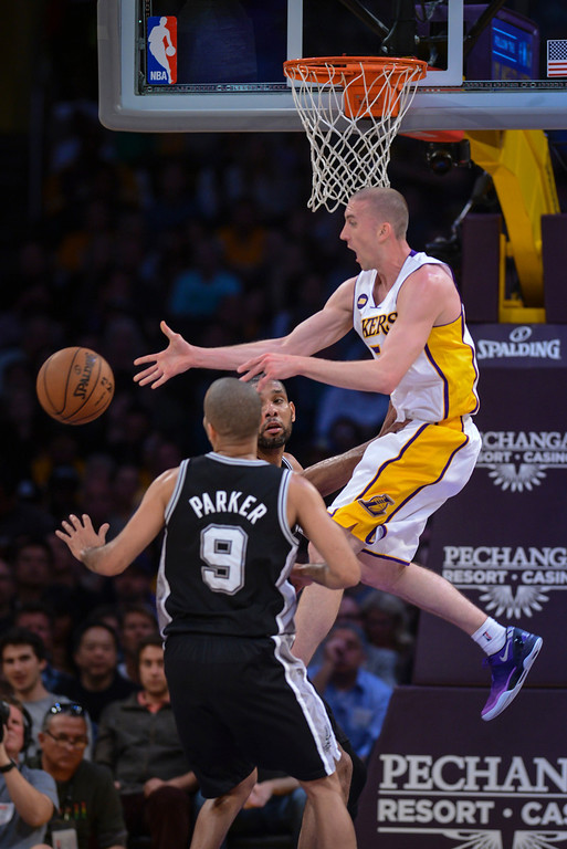 . Lakers\' Steve Blake passes off the ball to Dwight Howard as Spurs\' Tony Parker and Tim Duncan defend on the play during first half action at Staples Center Sunday.   Photo by David Crane/Los Angeles Daily News