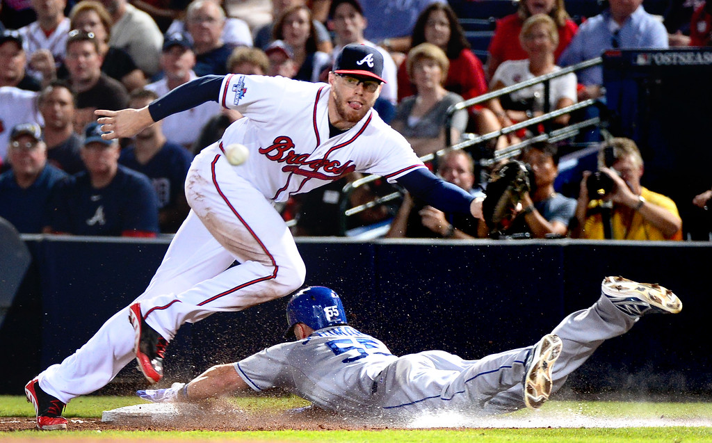 . Los Angeles Dodgers\' Skip Schumaker slides into first as  Atlanta Braves\' Freddie Freeman attempts to out him the seventh as the Braves defeat the Dodgers 4-3 in game 2 of the playoffs Thursday, October 4, 2013 at Turner Field in Atlanta, Georgia. (Photo by Sarah Reingewirtz/Pasadena Star- News)
