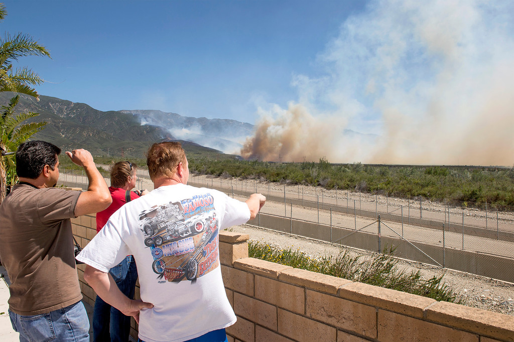 . Residents in the 5400 block of Carriage Place watch from a backyard as smoke from the Etiwanda Fire looms behind their homes in Rancho Cucamonga, Calif. April 30, 2014.  (Staff photo by Leo Jarzomb/San Gabriel Valley Tribune)