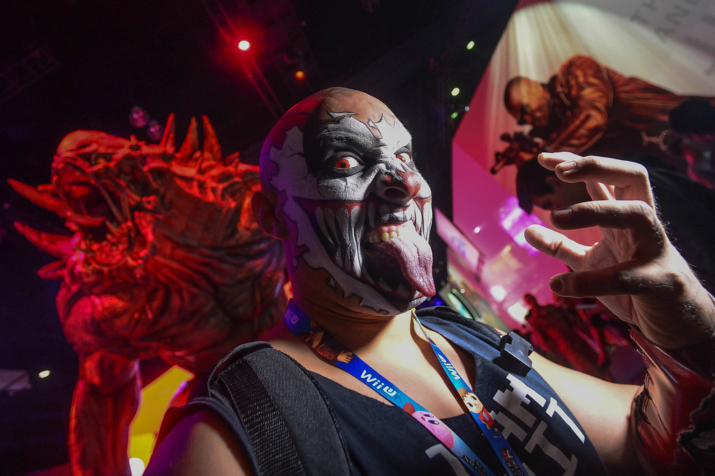""". Karcamo stands before a monster character from the video game \""""Evolve\"""" during Electronic Entertainment Expo in Los Angeles on Tuesday, June 10, 2014. (Photo by Watchara Phomicinda)"""