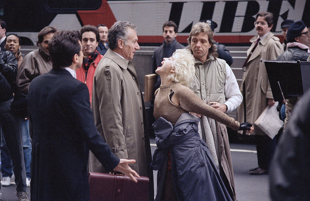". Madonna reacts for the camera during the filming of the movie ""Slammer\"" on Fifth Avenue while her co-star, Griffin Dunne, looks over her shoulder in New York, Nov. 12, 1986. In the romantic comedy, Madonna plays a paroled thief who, with her lawyer, Dunne, searches for the real criminal. (AP Photo/Richard Drew)"