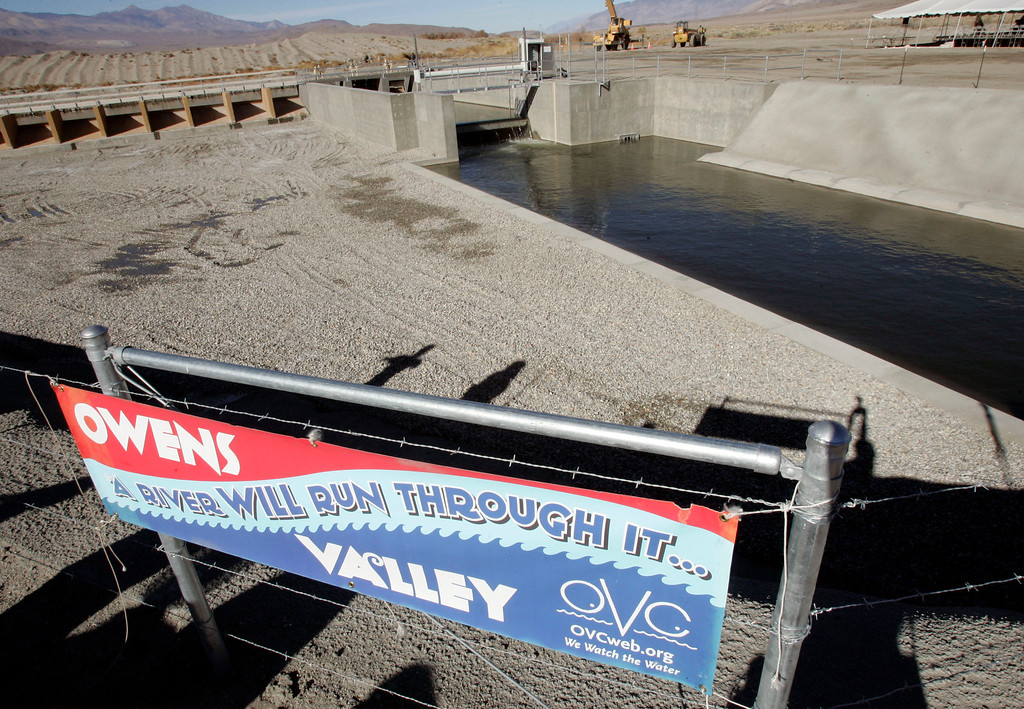 . A sign greets visitors to a diversion channel, background, that allows some Los Angeles Aqueduct water to enter a 62-mile stretch of the Owens River, which was a rushing stream generations ago before the aqueduct diverted its flow, in the Owens Valley in the eastern Sierra near Independence, Calif., Wednesday, Dec. 6, 2006. Water gushed into the long-dry Owens River on Wednesday as Los Angeles restored some of the flow it siphoned off for nearly a century. (AP Photo/Reed Saxon)