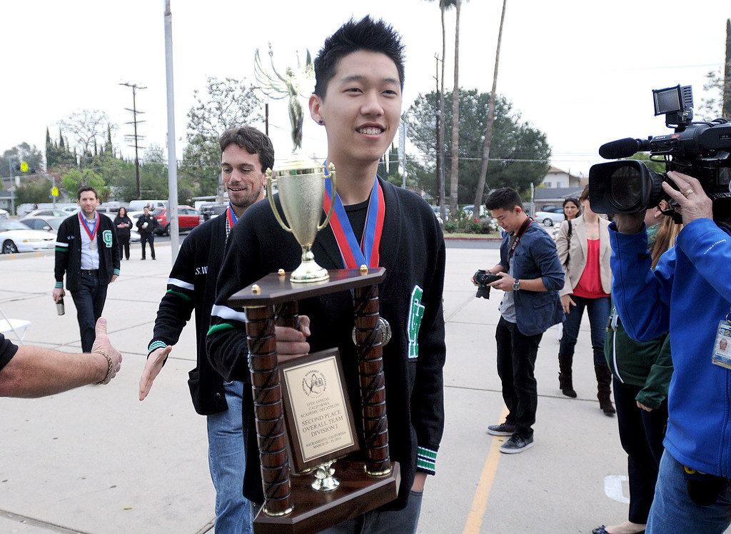 . The Granada Hills Charter High School Academic Decathlon team took second place in the California State Decathlon competition in Sacramento.  El Camino Real Charter High School finished first.  Both teams will travel to Hawaii for the National competition.  The Granada Hills team was greeted with a brief rally and comments from the school\'s Executive Director, Brian Bauer on Monday, March 24, 2014.  Mayson Lee carries the trophy.  (Photo by Dean Musgrove/Los Angeles Daily News)