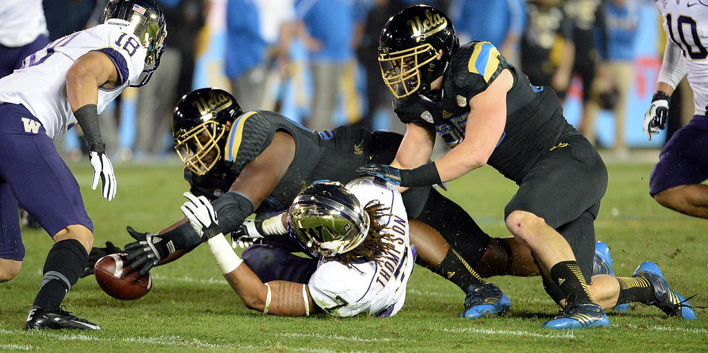 . UCLA Bruins recovers a Washington Huskies fumble during the first half of their college football game in the Rose Bowl in Pasadena, Calif., on Friday, Nov. 15, 2013. 