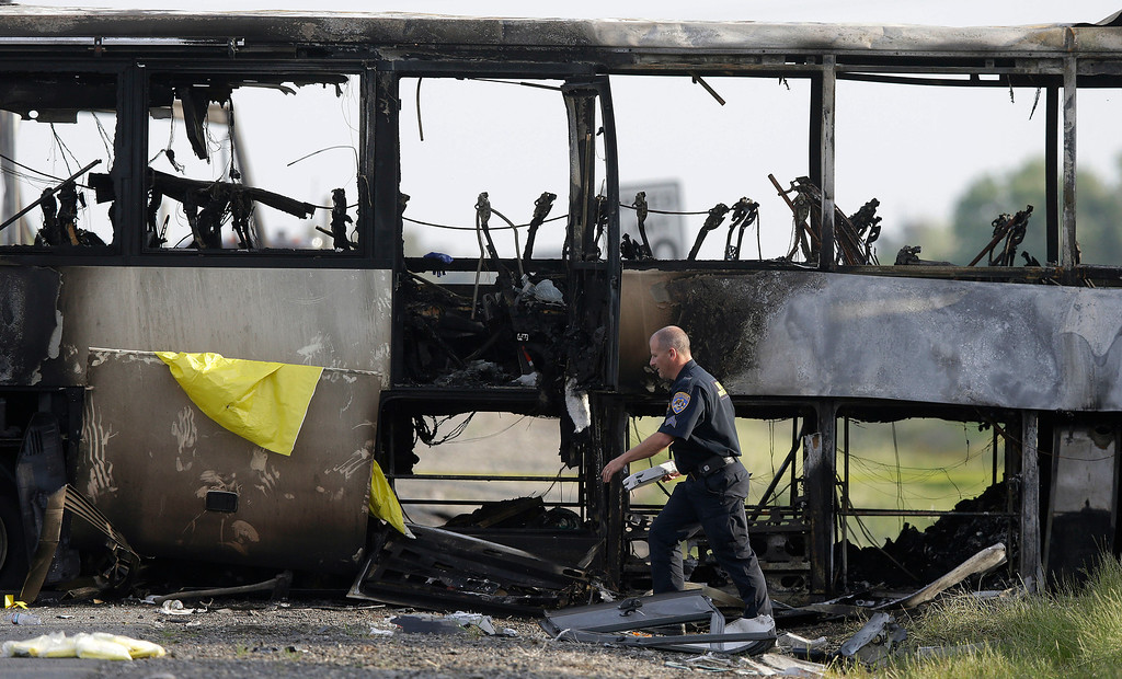 . A California Highway Patrol Officer walks past the remains of a tour bus that was struck by a FedEx truck on Interstate 5 Thursday in Orland, Calif., Friday, April 11, 2014. At least ten people were killed and dozens injured in the fiery crash between the truck and a bus carrying high school students on a visit to a Northern California College. (AP Photo/Jeff Chiu)