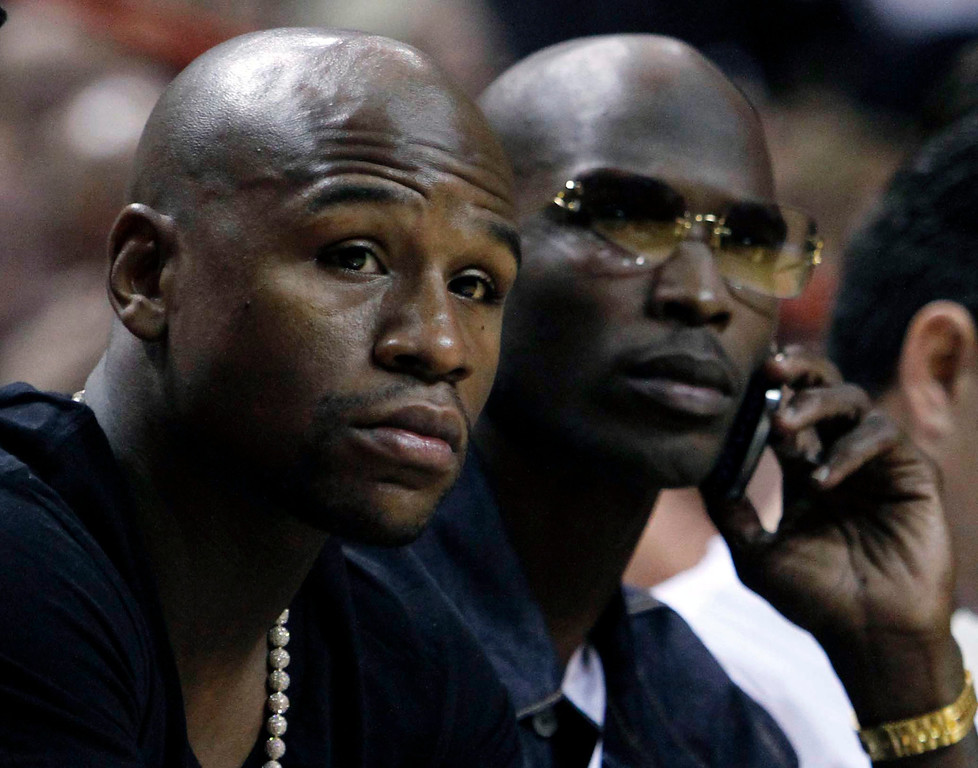 . Boxer Floyd Maywether Jr. and New England Patriots NFL football wide receiver Chad Ochocinco watch game action during the second half of an NBA basketball game between the New York Knicks and the Miami Heat, Thursday, Feb. 23, 2012 in Miami. Miami won 102-88. (AP Photo/Alan Diaz)