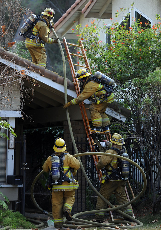 . Los Angeles County Firefighters climb a ladder to battle a fire that damaged a single family home. The fire started in the garage along the 1300 block of Via Verde. No injuries, but 5 cars were destroyed including two jaguars in San Dimas, Calif., on Saturday, Jan.4, 2014.   (Keith Birmingham Pasadena Star-News)