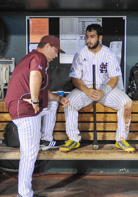 . Mississippi State\'s Nick Ammirati talks to assistant head coach Butch Thompson (30) as he sits in the dugout with the team\'s sledge hammer after losing 3-1 to UCLA in Game 1 of the NCAA College World Series baseball best-of-three finals, Monday, June 24, 2013, in Omaha, Neb., (AP Photo/Eric Francis)