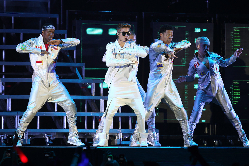 . Canadian pop singer Justin Bieber, center, performs on stage during the first Australian stop of his Believe tour at the Entertainment Centre in Brisbane, Australia, Wednesday, Nov. 27, 2013. (AP Photo/Tertius Pickard)