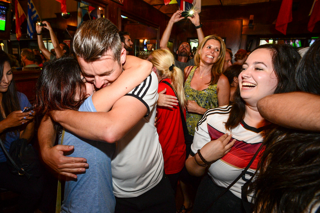 . Vivi Rama of West Hollywood, an Argentina fan, and German born Stefan Oriold, right, put away their differences and hug after Germany\'s World Cup win at 33 Tap\'s Sport Bar in Hollywood, CA Sunday, July 13. 2014.( Photo by David Crane/Los Angeles Daily News )