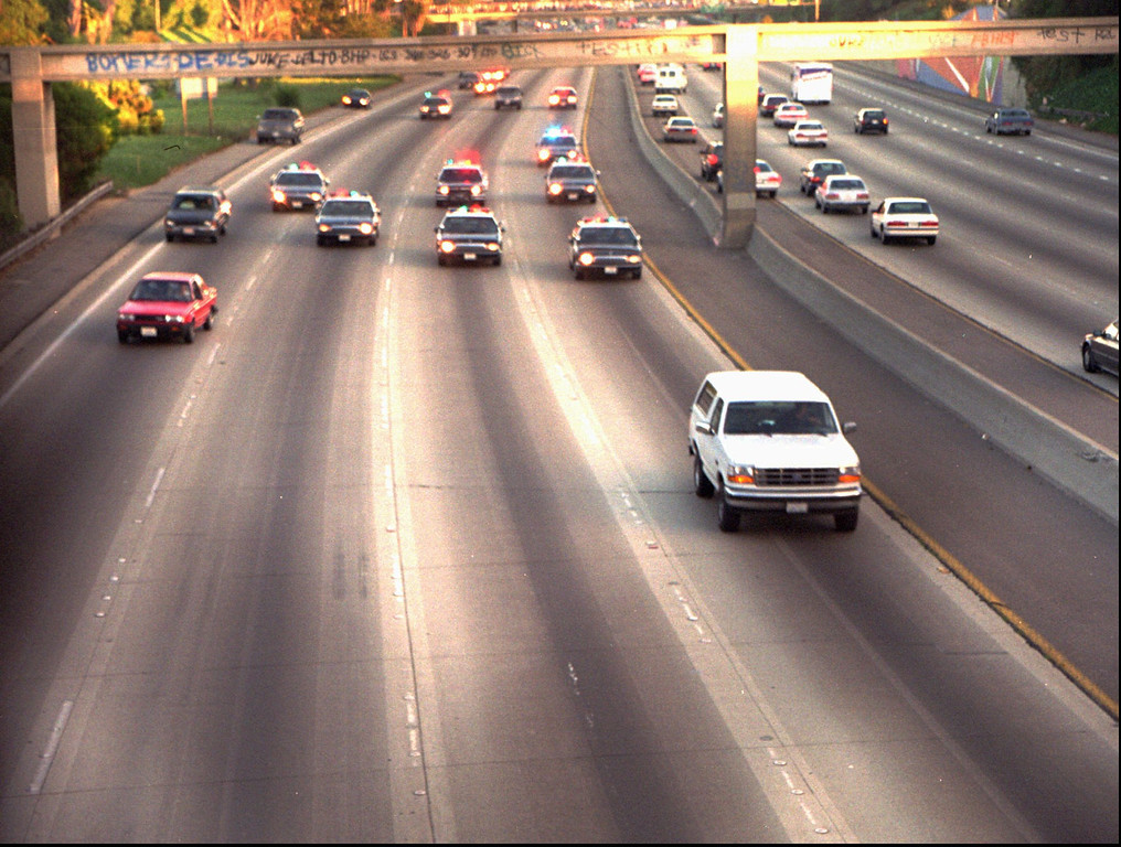 . A white Ford Bronco, driven by Al Cowlings and carrying O.J. Simpson, is trailed by police cars as it travels on a southern California freeway on June 17, 1994, in Los Angeles.  Cowlings and Simpson led authorities on a chase after Simpson was charged with two counts of murder in the deaths of his ex-wife and her friend.  (AP Photo/Joseph Villarin)