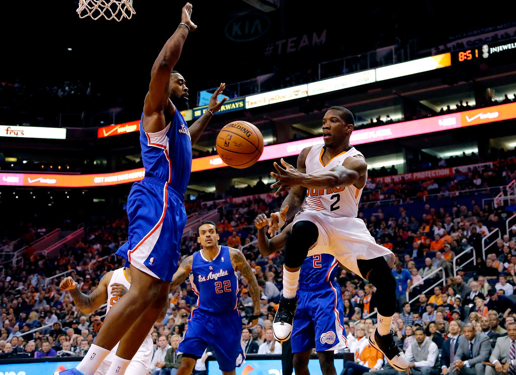 . Phoenix Suns guard Eric Bledsoe (2) passes around Los Angeles Clippers center DeAndre Jordan, left, during the second half of an NBA basketball game, Wednesday, April 2, 2014, in Phoenix. The Clippers won 112-108. (AP Photo/Matt York)