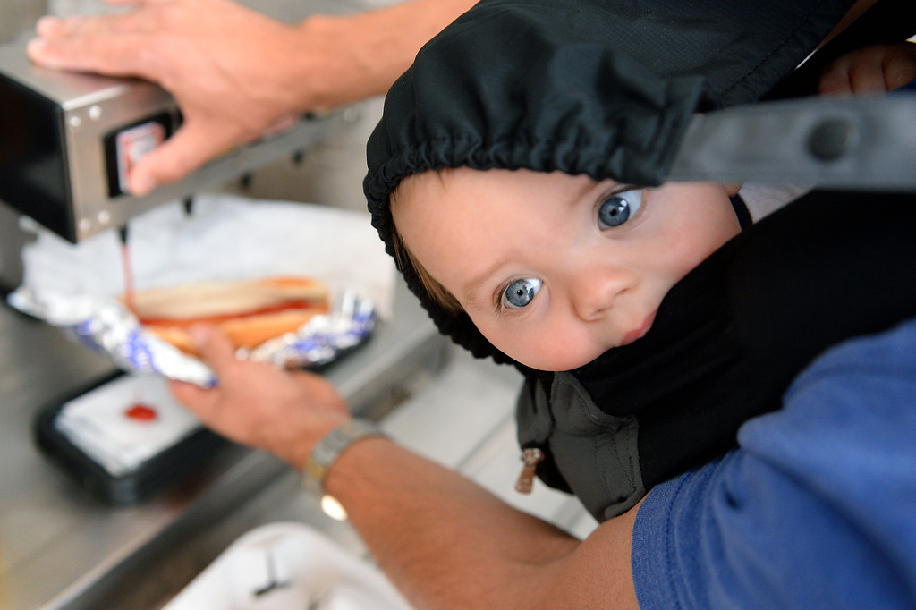 . Eight-month-old Parker Lemen peers out his carrier as his father Jeff Lemen prep a Dodger Dog at the Dodgers home opener, Friday, April 4, 2014, at Dodger Stadium. (Photo by Michael Owen Baker/L.A. Daily News)