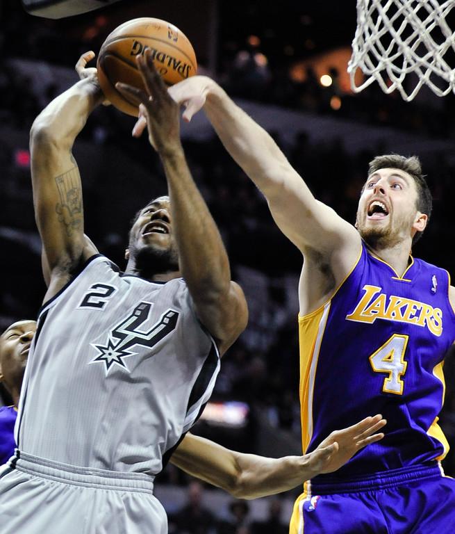 . Los Angeles Lakers forward Ryan Kelly, right, defends San Antonio Spurs forward Kawhi Leonard during the first half of an NBA basketball game Friday, March 14, 2014, in San Antonio. (AP Photo/Bahram Mark Sobhani)