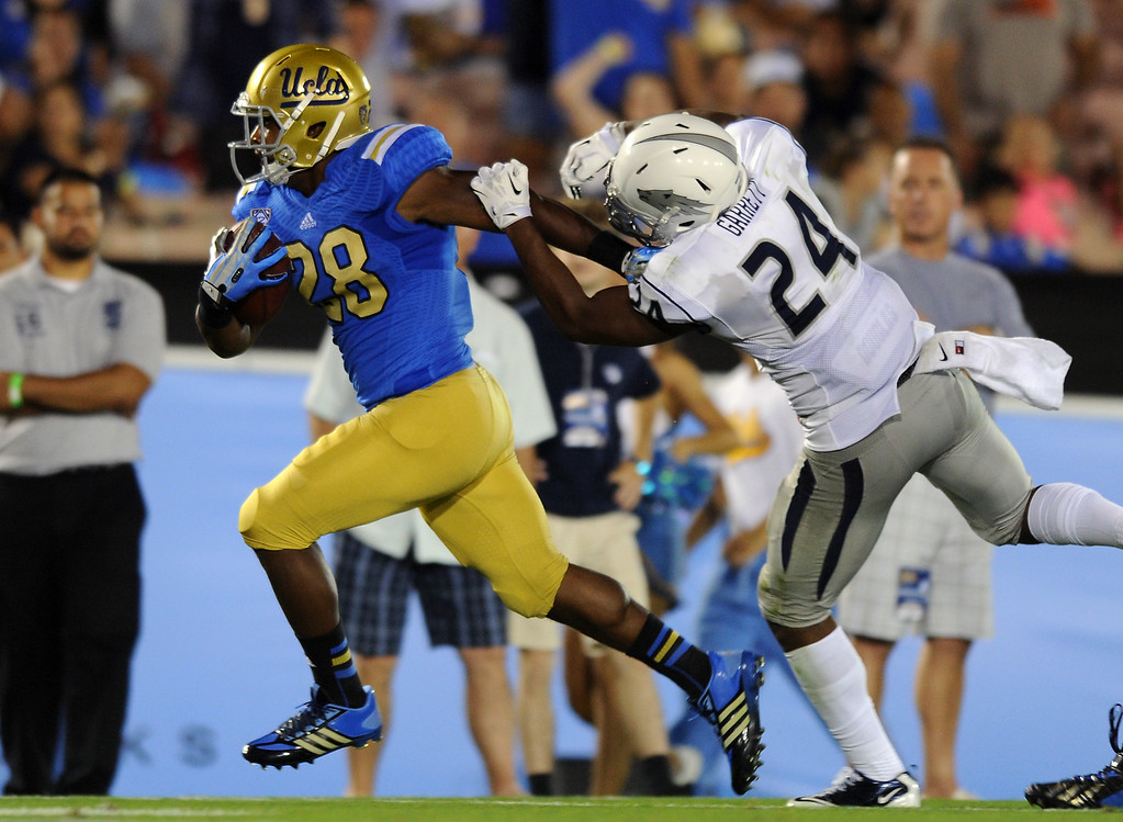 . UCLA RB Malcolm Jones shakes Nevada\'s Charles Garrett on a 28-yard score in the fourth quarter, Saturday, August 31, 2013, at the Rose Bowl. (Michael Owen Baker/L.A. Daily News)