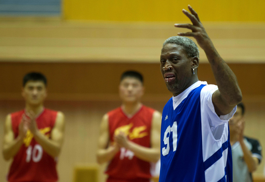 . Dennis Rodman waves after singing Happy Birthday to North Korean leader Kim Jong Un, seated above in the stands, before an exhibition basketball game with U.S. and North Korean players at an indoor stadium in Pyongyang, North Korea on Wednesday, Jan. 8, 2014. (AP Photo/Kim Kwang Hyon)