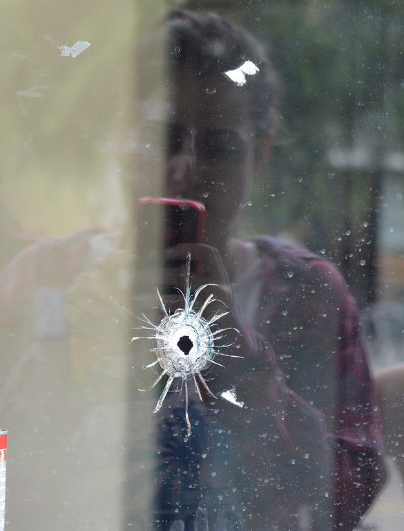 . May 24-,2014. Isla Vista, CA. UCSB students gather at IV Deli Mart where bullet holes are seen in the glass windows where one person was killed by the drive-by shooting that left seven people dead Friday night, including the attacker, and seven others wounded, authorities said Saturday.  The gunman got into two gun battles with deputies Friday night in the beachside community of Isla Vista before crashing his black BMW into a parked car. Photo by Gene Blevins/LA Daily News