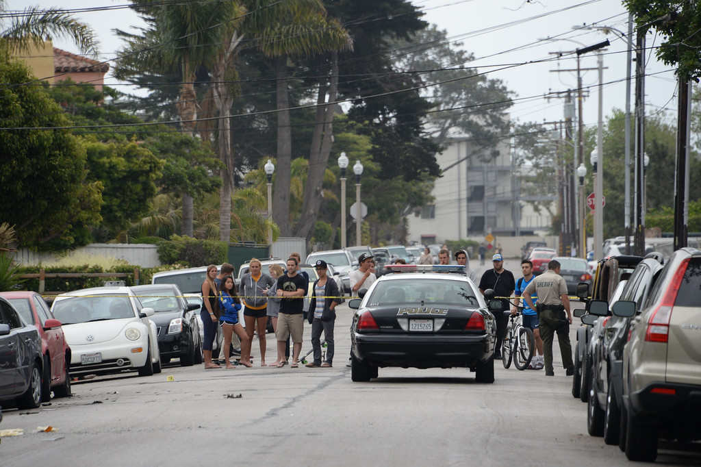". Police keep onlookers away from the scene where a car allegedly driven by a gunman crashed on May 24, 2014 in Isla Vista, California, a beach community next to the University of California Santa Barbara. Seven people, including the gunman, were killed  and seven others wounded in the May 23 mass shooting, Santa Barbara County Sheriff Bill Brown said Saturday. Brown said at a pre-dawn press conference that the shooting in the town of Isla Vista ""appears to be a mass murder situation.\"" Driving a black BMW, the suspect opened fire on pedestrians from his vehicle at several locations in the town. Police received their first emergency calls about the shooting around 9:30 pm Friday (0430 GMT Saturday).             (ROBYN BECK/AFP/Getty Images)"