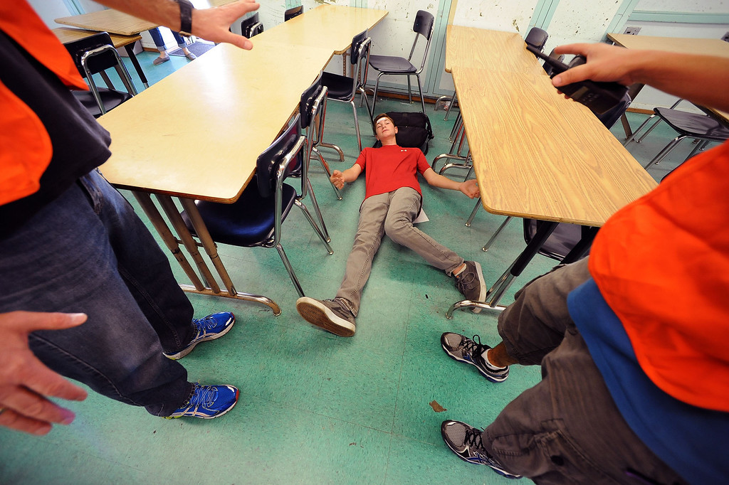 . RJ Schreck talks to a rescue team while portraying an injured student at Millikan Middle School during the Great American Shakeout in Sherman Oaks, CA, October 17, 2013.  (Andy Holzman/Los Angeles Daily News)