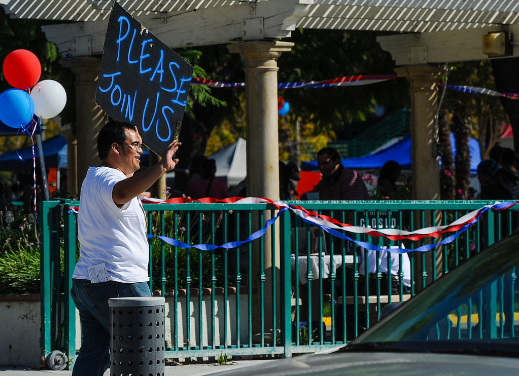 . Jorge Heredia, of San Bernardino Generation Now, tries to get passing motorists to join-in on the Turn Up the Vote event at Court Street Square in San Bernardino on Sunday, Oct. 20, 2013. Zealous Creative and San Bernardino Generation Now hosted the event in effort to encourage young adults to participate in the November 5 election. (Rachel Luna / San Bernardino Sun)
