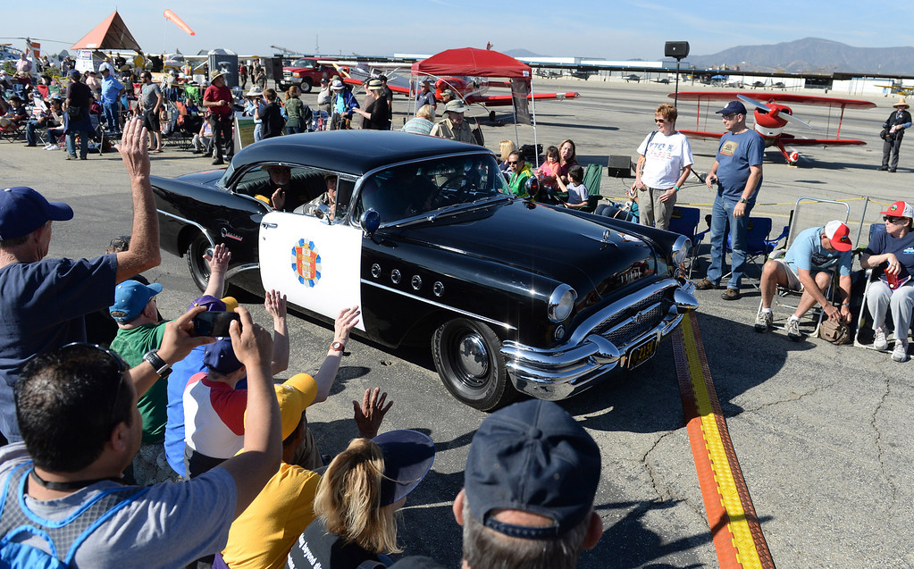 . Spectators wave as a 1955 Buick Century Highway Patrol car drives through during the Historical Vehicles Parade portion of the 39th annual Cable Airshow and Car Show at Cable Airport in Upland, Saturday, Jan. 11, 2014.(John Valenzuela/Staff Photographer)