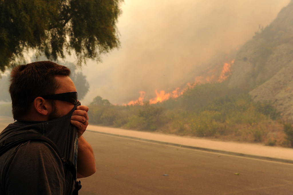 . Cal State University Channel Islands student Nathan Harmony watches as flames creep down the hills, Thursday, May 2, 2013. (Michael Owen Baker/Staff Photographer)