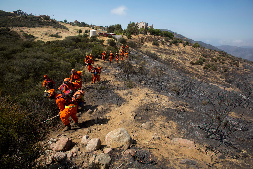 . Crews work on the fire line after a wildfire near Point Mugu, Calif., Saturday, May 4, 2013. High winds and withering hot, dry air was replaced by the normal flow of damp air off the Pacific, significantly reducing fire activity.  (AP Photo/Ringo H.W. Chiu)