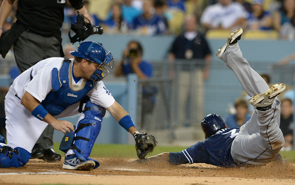 . Dodger catcher A.J. Ellis is late with the tag allowing Padres Rymer Liriano to score on a throwing error by Scott Van Slyke in the 2nd inning. The Dodgers played the San Diego Padres at Dodger Stadium. Los Angeles, CA. 8/20/2014(Photo by John McCoy Daily News)