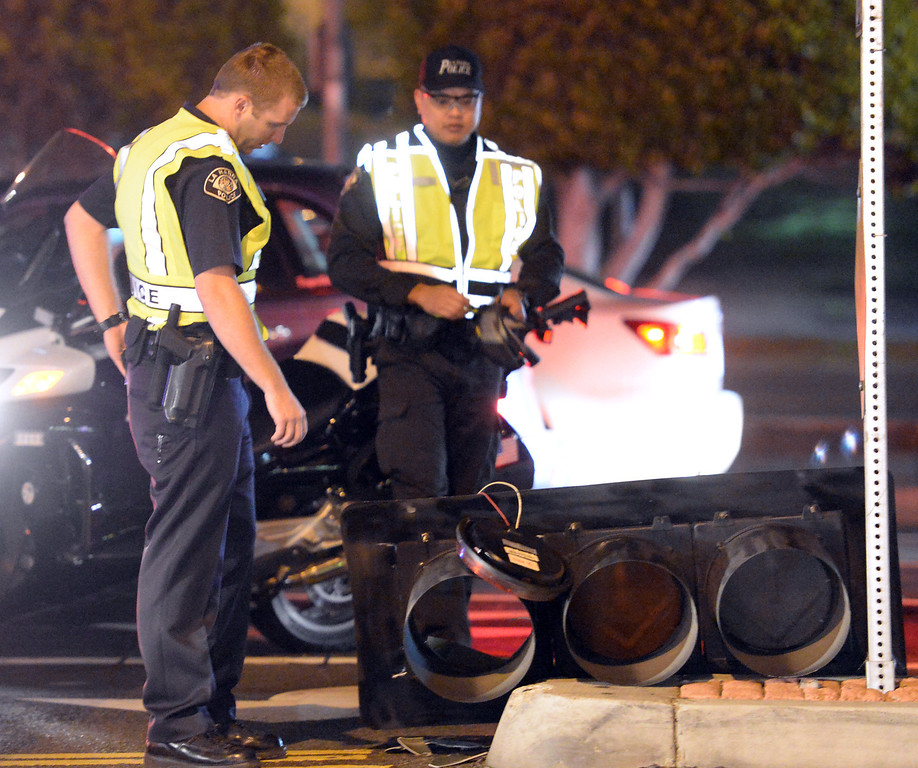 . La Habra Police officers look at a traffic signal that fell on traffic lanes at the intersection of Beach Boulevard and Lambert Road after the 5.1 earthquake in La Habra on Friday March 28, 2014. (Staff Photo by Keith Durflinger/Whittier Daily News)