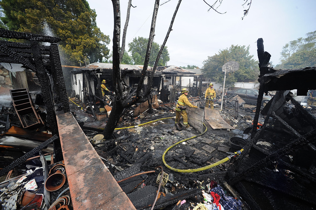 . Firefighters work to extinguish a structure fire that damaged two homes in the 17800 block of Vanowen St. in Reseda, CA April 10, 2014.(Andy Holzman/Los Angeles Daily News)