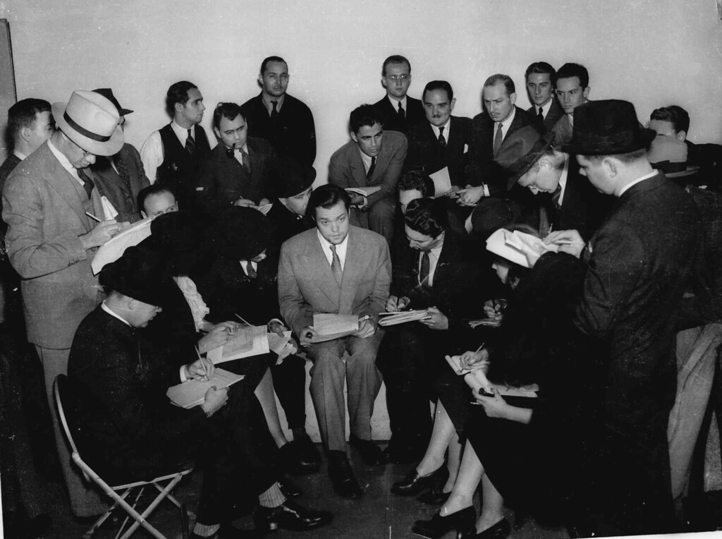 ". Orson Welles, center, young director who presented the dramatization of H.G. Wells\' ""War of the Worlds\"" on Sunday night, Oct. 30, 1938 speaks with the press the next day.  The radio broadcast caused great panic among radio listeners amazed that his dramatization had been so realistic.   (AP Photo)"