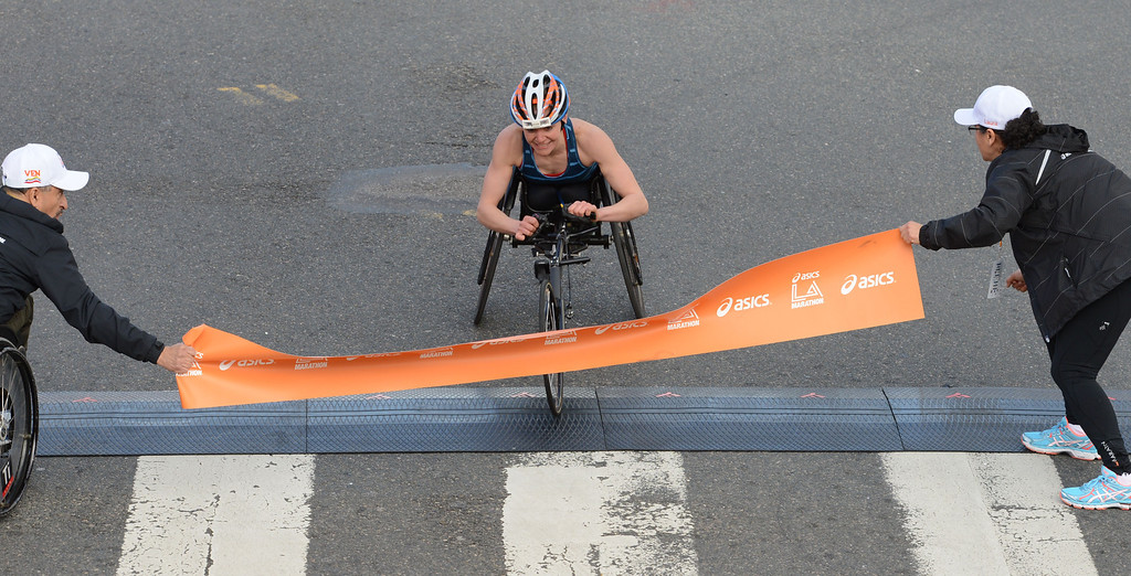 . 2014 ASICS LA Marathon women\'s wheelchair winner Susannah Scaroni  crosses the finish line in Santa Monica Calif, with a time of 1: 54: 54.   Sunday, March 9,  2014.   (Photo by Stephen Carr / Daily Breeze)