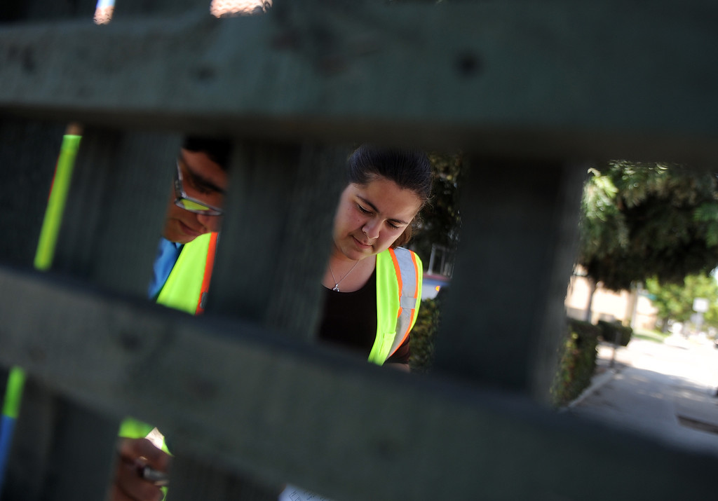 . Interns Monserrat Marquez, right , a former El Rancho graduate along with Robert Sanchez a La Serna graduate inspect a bus stop at the corner of Passons Blvd and Jackson Street as part of the Pico Rivera college prep program on Tuesday, July 16, 2013 in Pico Rivera, Calif.   (Keith Birmingham/Pasadena Star-News)