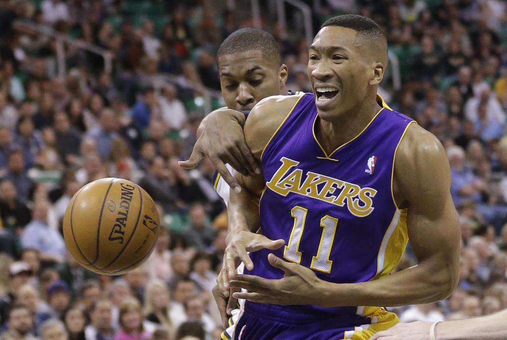 . Utah Jazz\'s Derrick Favors, rear, fouls Los Angeles Wesley Johnson (11) in the second quarter during an NBA basketball game Monday, April 14, 2014, in Salt Lake City, Utah. (AP Photo/Rick Bowmer)