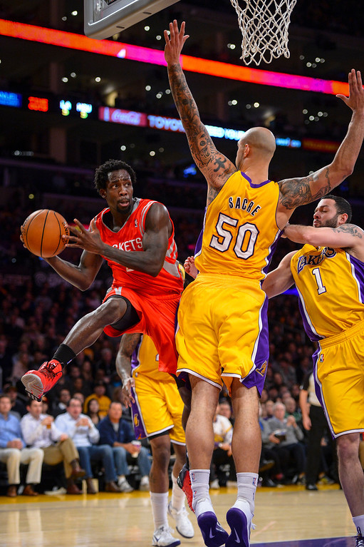. Rockets� Patrick Beverley makes a pass around Lakers� Robert Sacre and Jordan Farmar during first half action at Staples Center Wednesday, February 19, 2014. ( Photo by David Crane/Los Angeles Daily News )