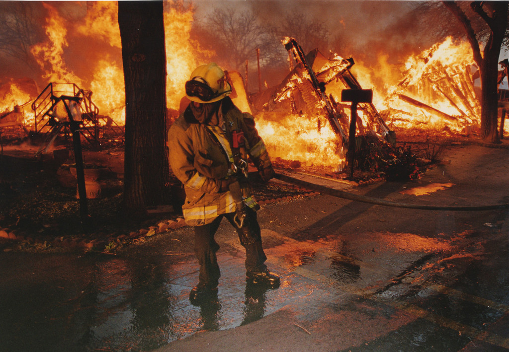 . A firefighter pulls a hose through the Tahitian Mobile Park in Sylmar, CA. 1/17/1994, photo by (John McCoy/Los Angeles Daily News)