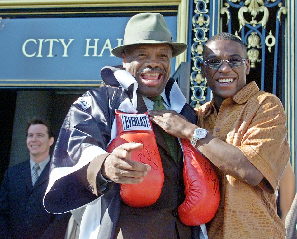 ". San Francisco Mayor Willie Brown, left, wearing a robe and boxing gloves, stands outside City Hall with WBC super featherweight champion ""Pretty Boy\"" Floyd Mayweather Jr., right, in San Francisco, Thursday, Nov. 8, 2001.  The mayor was promoting Mayweather\'s title fight against Jesus \""El Matador\"" Chavez which is scheduled to take place in San Francisco, Saturday night.  The bout will be the first major fight to be held in San Francisco in 40 years. (AP Photo/Eric Risberg)"