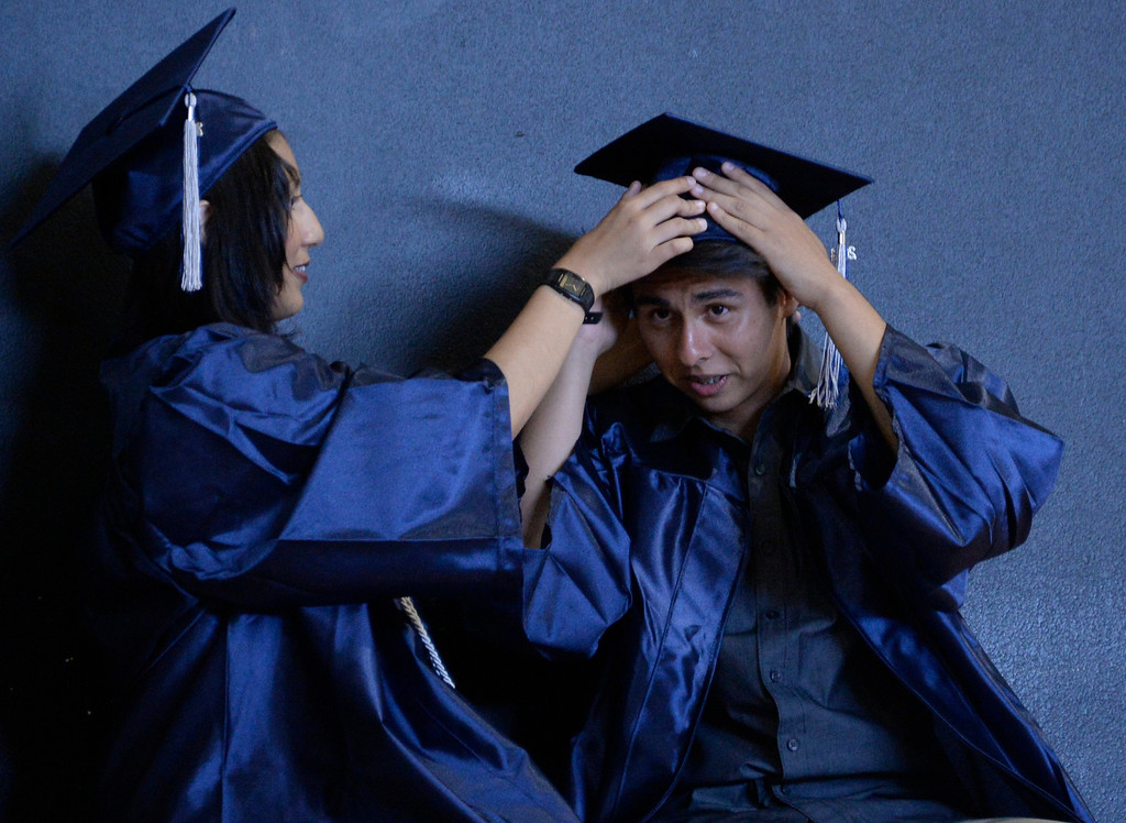 . June 6,2014 PANORAMA city, California. Grads help each other getting their hats on right, during the Panorama High graduating class of 2014. Photo by Gene Blevins/LA Daily News