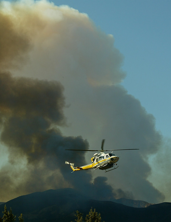. 10-24-03...Val Verde Park fire...Photo of LA county helicopter as it comes in for water as two headers of smoke go up into the air from 2 different fires, Del Valle and Piru fire,  the Del Valle is 200+acre brush fire that is still burning, more info from fire dept.Photo by Gene Blevins/LA Daily news